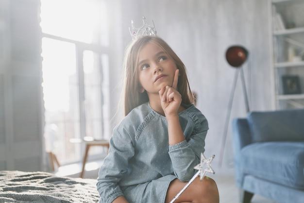 Wat als... schattig klein meisje dat haar hand op haar kin houdt en wegkijkt terwijl ze thuis tijd doorbrengt