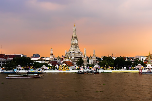 Wat arun-tempel met chao phraya-rivier bij zonsondergang in bangkok, thailand