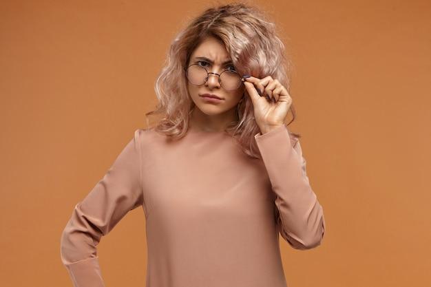 Wat bedoelde je? schot van strikte modieuze jonge europese vrouwelijke leraar met krullend haar fronsen en verlagen van haar stijlvolle brillen