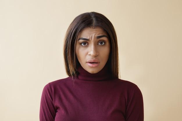 Wat bedoelt u. portret van een verwarde jonge afro-amerikaanse vrouw die zich verbaasd en verontwaardigd voelt, één wenkbrauw optrekt en de mond open houdt, verwarring, misverstand of ontevredenheid uitdrukt