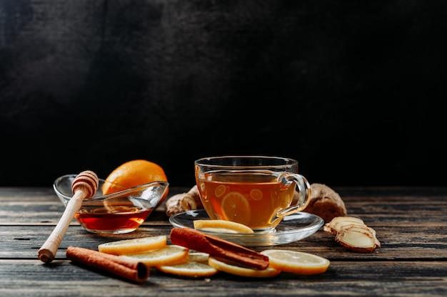 Wat citroen met gember, honing, droge kaneel, thee op donkere houten en zwarte achtergrond, zijaanzicht. ruimte voor tekst