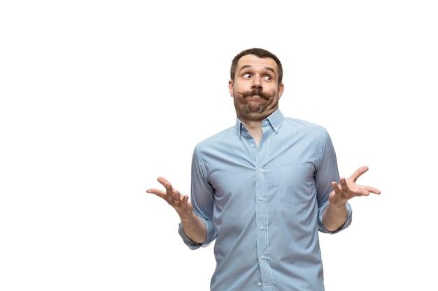 Wat dan ook jonge blanke man met grappige ongebruikelijke populaire emoties en gebaren geïsoleerd