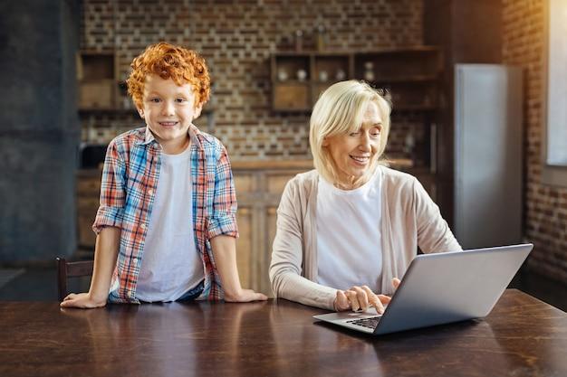 Wat doe je hier. schattige roodharige jongen lachend in de camera terwijl leunend op een tafel naast zijn vrolijke oma met behulp van haar laptop thuis.