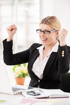 Wat een geluksdag! gelukkig volwassen zakenvrouw zittend op haar werkplek en gebaren