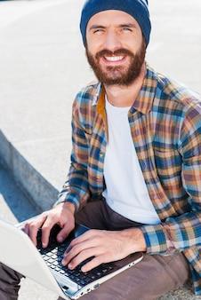 Wat een heerlijke dag om buiten te werken! knappe jonge, bebaarde man die lacht terwijl hij op een laptop werkt en naar de camera kijkt