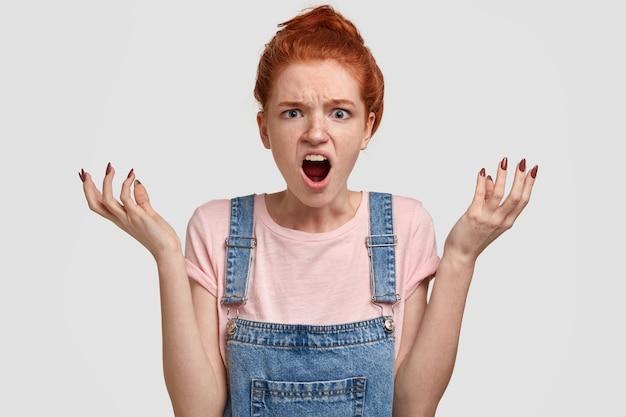 Wat een hel! depressieve verbaasde roodharige vrouw met boze geïrriteerde gezichtsuitdrukking, spreidt handen, roept uit van ergernis, heeft woedende blik, geïsoleerd over witte muur. negatieve emoties