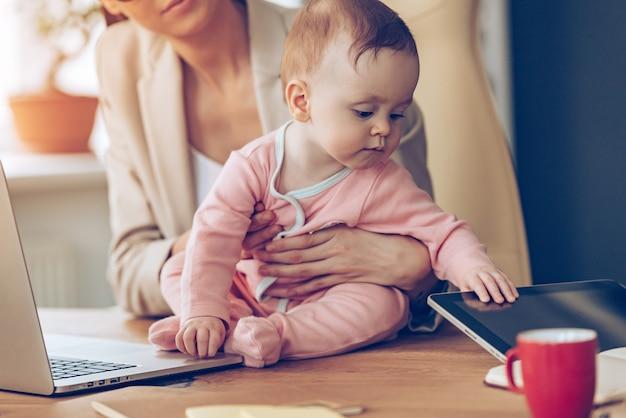 Wat een interessant speelgoed! close-up deel van een klein babymeisje dat digitale tablet vasthoudt terwijl ze op haar moeders werkplek zit
