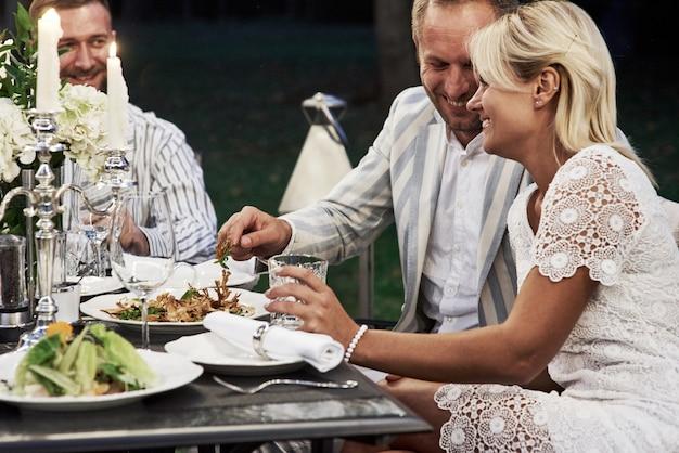 Wat een leuk stel. groep volwassen vrienden hebben 's avonds een rust en een gesprek in de achtertuin van het restaurant.