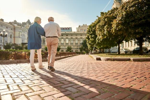Wat een mooie dag achteraanzicht van een bejaard stijlvol stel dat samen buiten loopt
