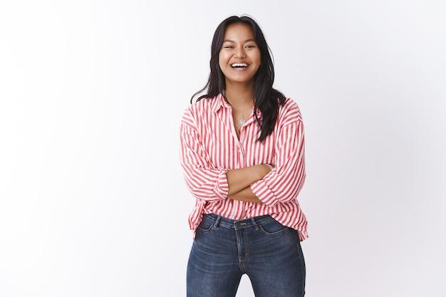 Wat een mooie dag. portret van een vrolijk vrolijk en energiek schattig maleisisch meisje in een roze gestreepte blouse die plezier maakt, een grapje maakt, een grappig gesprek heeft, glimlacht en lacht om de camera over de witte muur