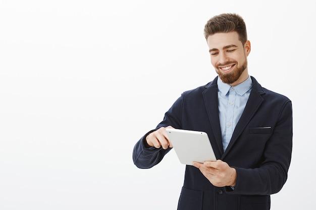 Wat een plezier om naar een bankrekening vol geld te kijken. opgetogen knappe en succesvolle zakenman met baard en nette kapsel in pak met digitale tablet glimlachend tevreden kijken apparaatscherm