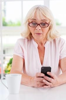 Wat een verrassing! verrast oudere vrouw die naar haar mobiele telefoon kijkt en een gezicht trekt terwijl ze aan tafel zit