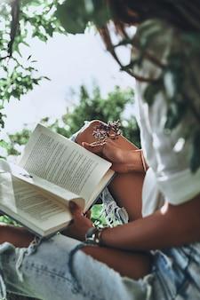 Wat gaat er nu gebeuren? close-up van een jonge vrouw die een open boek vasthoudt terwijl ze tijd buitenshuis doorbrengt
