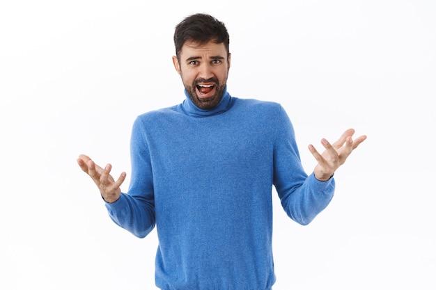 Wat gebeurt er in godsnaam. portret van een verwarde en gefrustreerde, gehinderde blanke man, handen omhoog gespreid in ontzetting, teleurgesteld en overstuur starend, klagend over een slechte zaak, witte muur