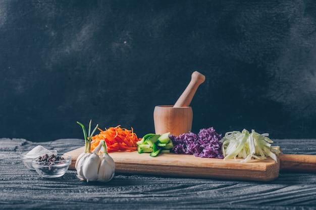 Wat gehakte kool met andere groenten in een scherpe raad op donkere houten achtergrond, zijaanzicht.