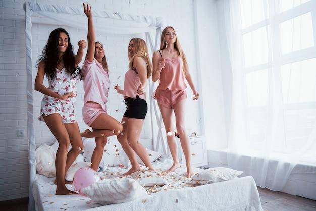 Wat gek dansen. confetti in de lucht. jonge meisjes hebben plezier op het witte bed in een mooie kamer