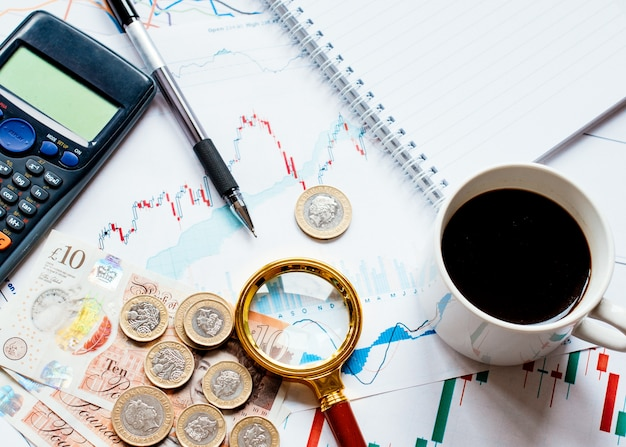 Wat geld (dollar, cent, pond) rekenmachine, kop koffie, loep en verschillende geldgrafieken op tafel