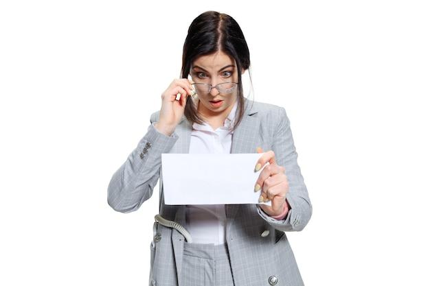 Wat heb ik de hele maand gedaan. jonge vrouw in grijs pak krijgt een klein salaris en gelooft haar ogen niet. geschokt en verontwaardigd. concept van de problemen, zaken, problemen en stress van de kantoormedewerker.