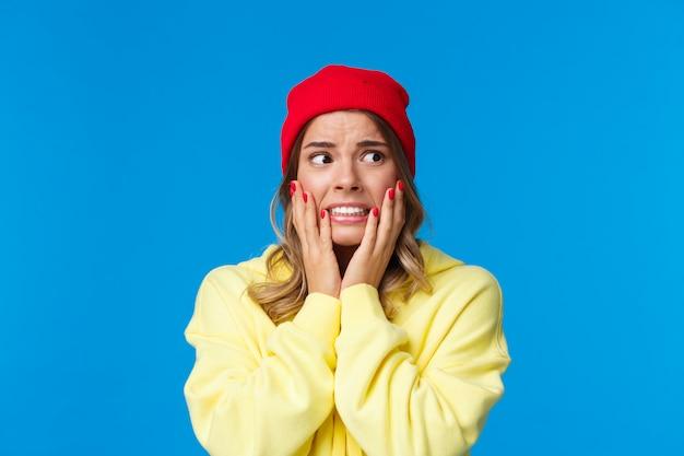 Wat heb ik gedaan. bezorgd en bezorgd angstige blanke vrouw in rode muts en gele hoodie, houdt haar handen op de wangen in paniek, kijkt angstig weg, staat onrustige blauwe muur