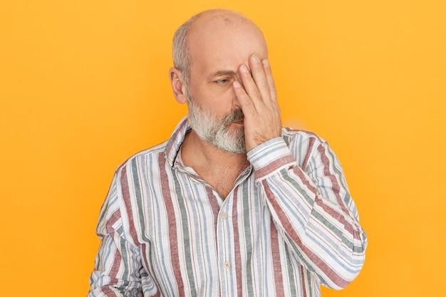 Wat heb ik gedaan. portret van bedroefd ongelukkig bejaarde man met kaal hoofd met beschaamde spijtige uitdrukking, gezicht bedekt met hand.