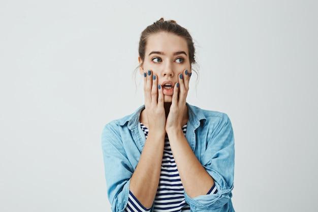 Wat heb ik gedaan. studio die van ongerust gemaakte en zenuwachtige kaukasische handen van de vrouwenholding op gezicht is gemaakt en opzij met geopende mond en verwarde bezorgde uitdrukking kijkt. meisje heeft een fout gemaakt