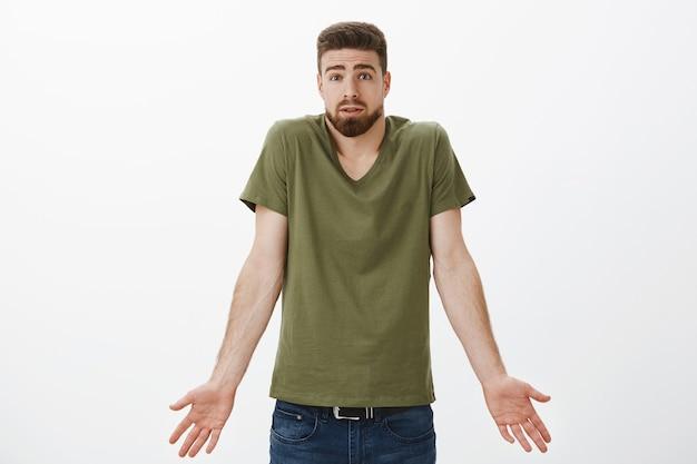Wat heb ik verkeerd gedaan. portret van verwarde vriend kan niet begrijpen wat er is gebeurd terwijl hij zijn schouders ophaalt en de handen opzij vasthoudt, wenkbrauwen optrekt zich gefrustreerd en ondervraagd voelt terwijl hij zich probeert te verontschuldigen