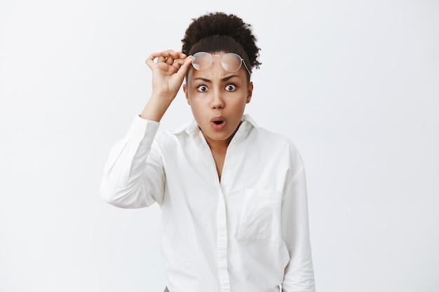 Wat heb je gedaan. portret van schudde intense afro-amerikaanse vrouw die ongelooflijke en vreselijke puinhoop zag, bril opstijgt, lippen vouwt en fronst, kan niet begrijpen wat er is gebeurd, geschokt is