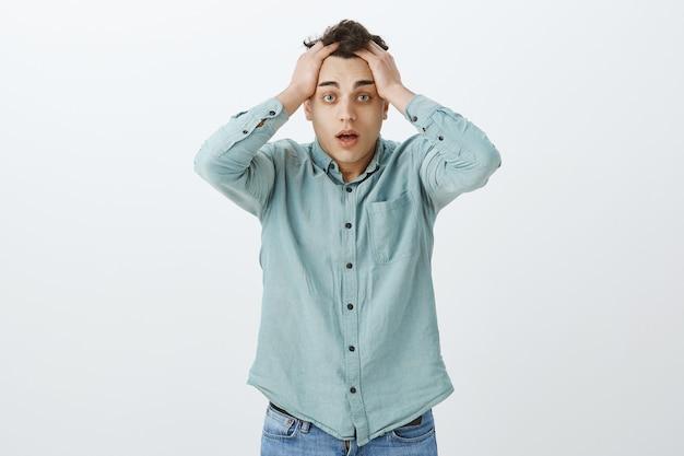 Wat heb je gedaan. portret van verbijsterde ontevreden jonge man in casual shirt