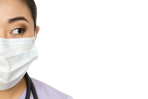 Wat hebben we hier? bijgesneden studio halve gezicht close-up van een vrouwelijke arts chirurgisch masker dragen kijken naar de kopie ruimte aan de zijkant