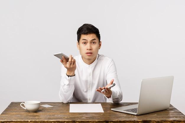 Wat, ik ben aan het telefoneren. geërgerde en gehinderde aziatische zakenman onderbrak belangrijk gesprek, kijkend geïrriteerde het stellen van vraag, houdend smartphone