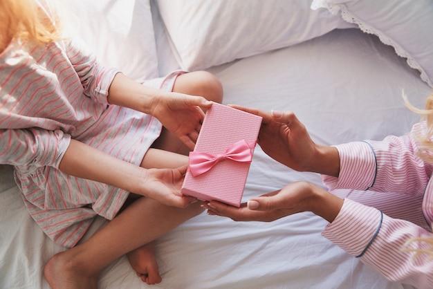 Wat is daar? close-up bovenaanzicht van jonge moeder die een cadeautje geeft aan haar dochtertje terwijl ze thuis op het bed zit