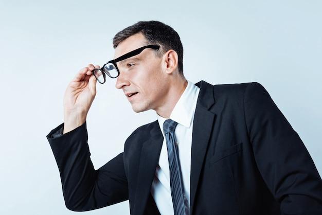 Wat is dat. zijaanzicht van een geconcentreerde werknemer die zijn bril gebruikt terwijl hij zijn aandacht ergens op richt en er aandachtig naar kijkt.