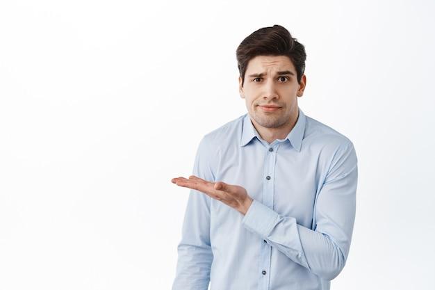 Wat is dit. verwarde zakenman, kantoormedewerker die de hand opzij wijst naar iets vreemds, in een blauw shirt staat en verbaasd naar de voorkant kijkt, witte muur