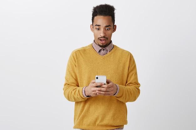 Wat is er aan de hand. portret van geschokt en verbijsterd aantrekkelijke afro-amerikaan, kaak laten vallen, verward en verrast zijn tijdens het lezen van artikel op internet via smartphone over grijze muur