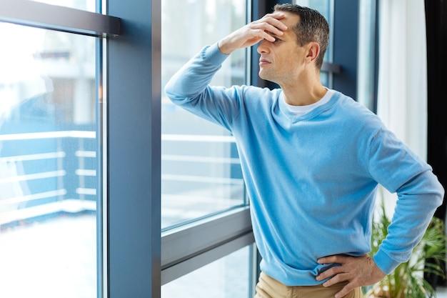 Wat is er buiten? trieste humeurige ongelukkige man die bij het raam staat en erin kijkt terwijl hij zijn voorhoofd vasthoudt