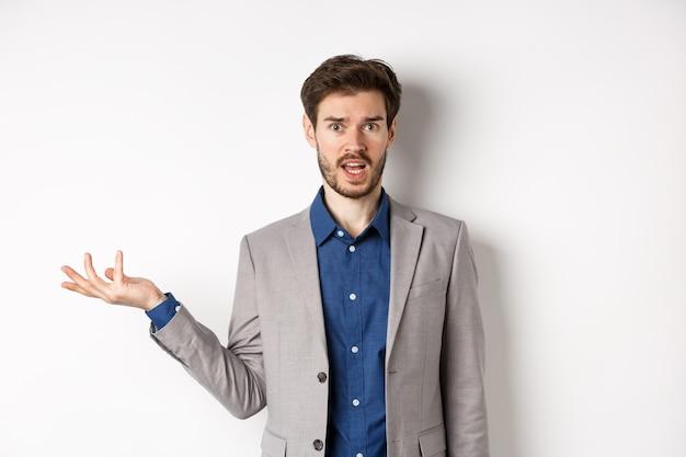 Wat is er verkeerd. verwarde man in pak kan het niet begrijpen, ziet er geen idee uit met opgeheven hand, starend naar de ondervraagde camera, staande op een witte achtergrond.