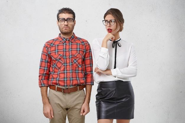 Wat is hij saai! ontevreden vrouwelijk model kijkt naar haar nerd-vriendje, verveelt zich met hem