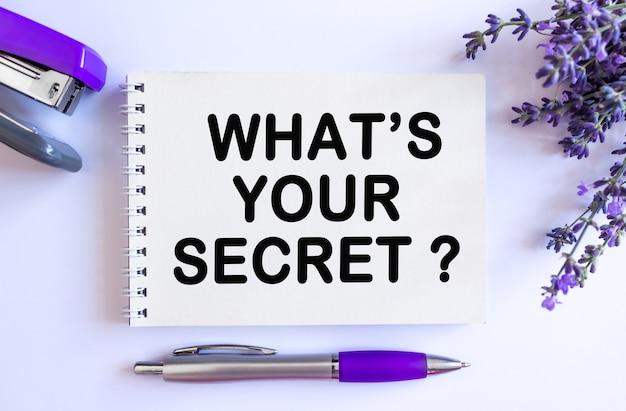 Wat is je geheime tekst... bovenaanzicht van open blanco notitieblok met lavendelboeket op witte achtergrond