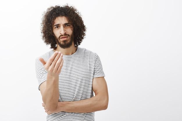 Wat is uw punt man. ontevreden vriendje met baard en afro-kapsel, handpalm schuddend