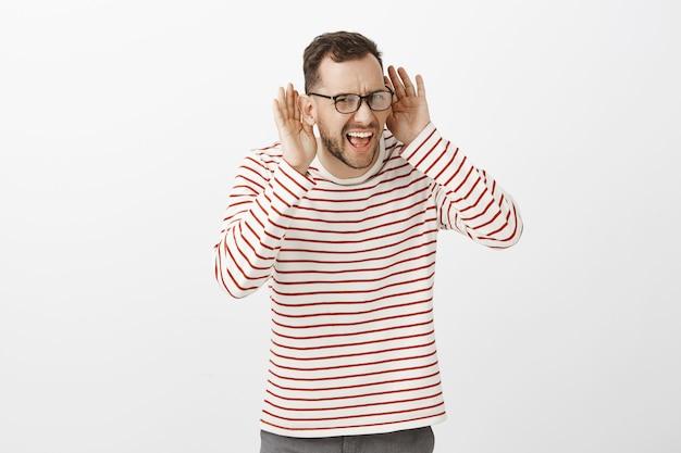 Wat kan je niet horen. portret van ongemakkelijke intense knappe volwassene met varkenshaar in glazen