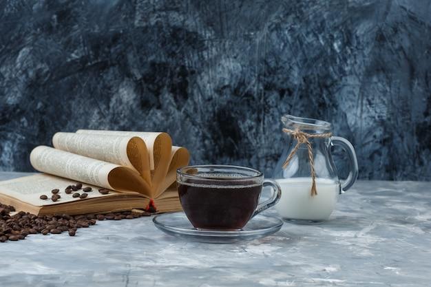 Wat koffie met koffiebonen, boek, melk in een kop op grunge en gipsachtergrond, zijaanzicht.
