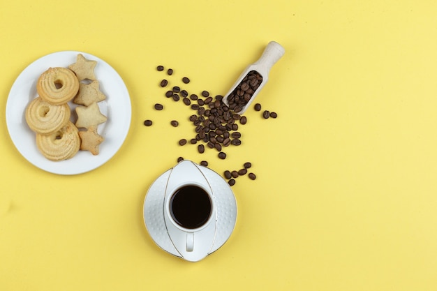Wat koffie met koffiebonen en koekjes op gele achtergrond