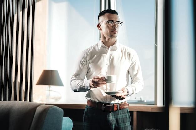 Wat koffie. stijlvolle jonge rijke zakenman die donker vierkant overhemd draagt dat wat koffie drinkt
