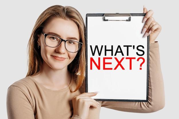 Wat komt hierna. mooie jonge zakenvrouw met een bril houdt een klembord vast met mock-up ruimte geïsoleerd op een grijze achtergrond