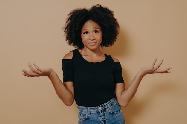 Wat moet ik nu doen. verward, onbewust afro-vrouw met golvend krullend haar, steekt handen in verbijstering op, ziet er verward uit, kan geen beslissing nemen, geïsoleerd over beige studioachtergrond met kopieerruimte