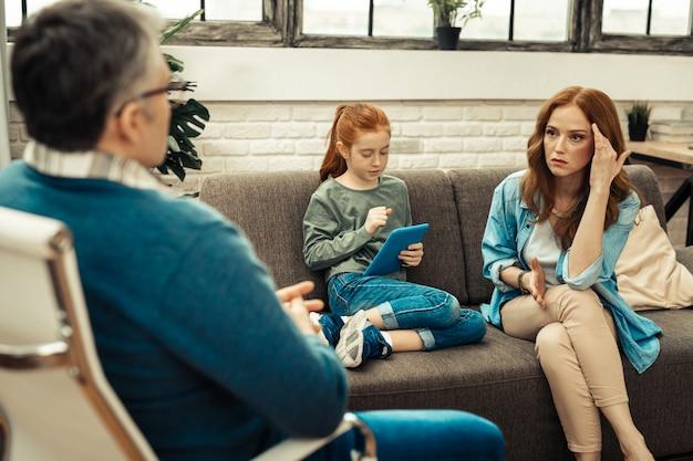 Wat moeten we doen. ernstige bezorgde vrouw die naar de professionele therapeut kijkt terwijl ze met hem over haar dochter praat