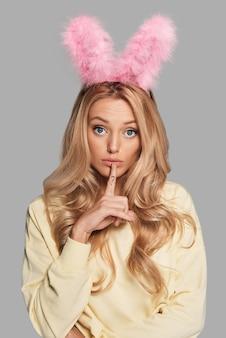 Wat moeten we doen? verwarde jonge vrouw in roze konijnenoren die wijsvinger op haar lippen houdt terwijl ze tegen een grijze achtergrond staat