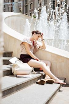 Wat te doen. aangename jonge vrouw die bij de fontein zit terwijl ze denkt wat ze moet doen