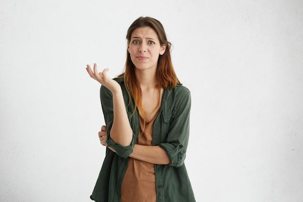 Wat? terloops geklede verbaasde vrouw die bij een lege muur staat, een twijfelachtige blik heeft, haar gezichtsemoties en gebaar verontwaardiging, afkeer en onzekerheid over iets uitdrukt