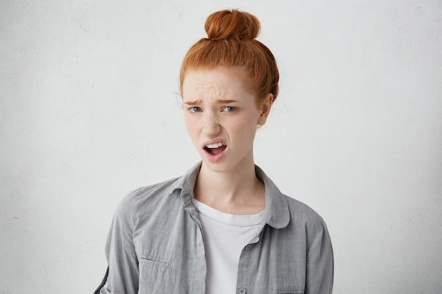 Wat? verontwaardigde jonge mooie vrouw met haarknoop, gekleed in vrijetijdskleding die bij een grijze muur staat, grimassen, uitdrukking geeft aan haar afkeer of minachting, onwil voelt jegens iets